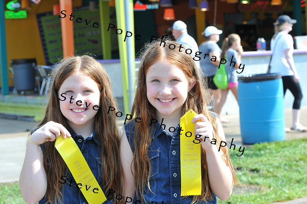 Nine year olds Grace and Autumn Glosser, of Ottumwa, show the ribbons they earned in the Twins, Triplets, and More Contest at the Iowa State Fair on Aug. 11. (Steve Pope Photography/ Iowa State Fair)