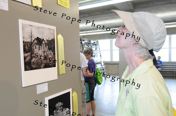 Joyce Bahrenfus, of Ogden, views photography on display at the Iowa State Fair on Aug. 12. (Steve Pope Photography/ Iowa State Fair)