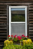 A cottage window with decorative flowers at the Little Red Wagon shop in the Amana Colonies, Iowa, USA.