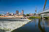 The Des Moines River Dam and downtown pedestrian bridge in Des Moines, Iowa, USA.