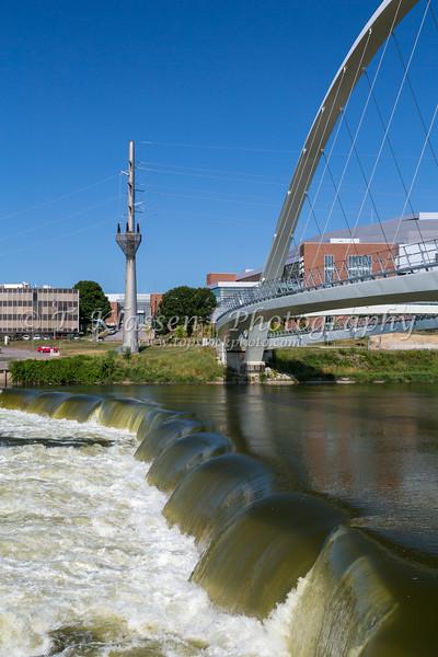 The Des Moines River Dam and downtown pedestrian bridge in Des Moines, Iowa, USA.
