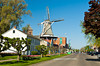 A canal and windmill in downtown Pella at the Tulip Time Festival in Pella, Iowa, USA, America.