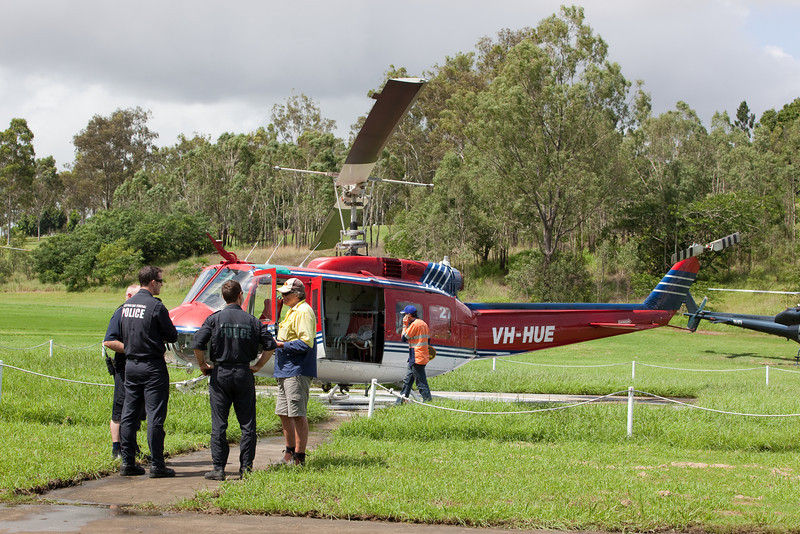Australian Federal Police updating helicopter pilot at Ipswich Helipad, Limestone Park - 12 Jan 2011