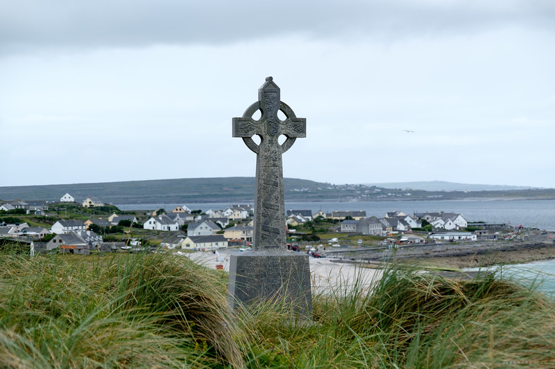 Cross with the homes of Inisheer in the background.
