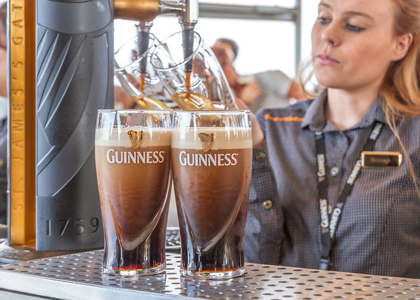 Guinness Brewery - Freshly poured Glasses of Guinness in the Gravity Bar in focus and server filling 2 in the rear OOF - Dublin Ireland