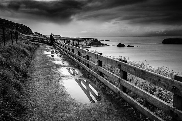 View of people on the path by Carrick-A-Rede Rope Bridge at the Causeway Coastline - Ballintoy, County Antrim Northern Ireland BW Contrast