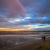 Couple walking on the Dublin Bay at low tide under a rainbow in the early evening - Dublin Ireland
