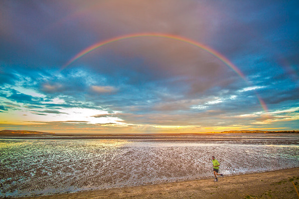 Jogger on Dublin Bay at low tide under a rainbow in the late afternoon - Dublin Ireland