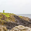 Giant's Causeway basalt hexagon formations and person in yell0ow slicker on top - County Antrim Northern Ireland