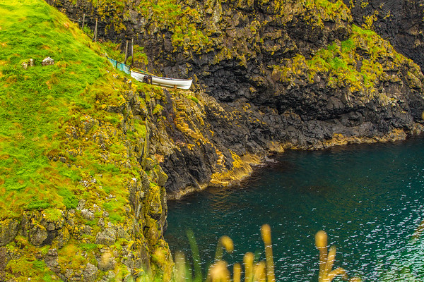 Fishing boat on the cliff face with stairs going down to the water off the Causeway Coastline - Ballintoy, County Antrim Northern Irelan  - 2d