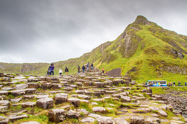 Giants causeway - people on Basalt rocks with hill behind - County Antrim Northern Ireland