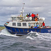 MV Jack B Boat in the Atlantic Ocean riding over swells  coming to shore at the Cliffs of Moher County Clare - Ireland