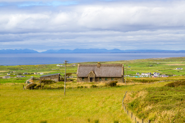 House in Irish field overlooking houses in the distance and the ocean further off in County Clare - Ireland