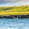 Doonagore Castle on the cliffs of Moher with waterfall in Doolin County Clare seen from the ocean - Ireland - 2