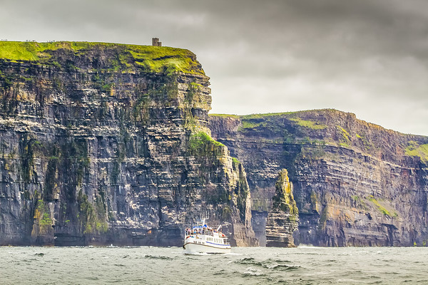Queen of Aran boat in the Atlantic Ocean under the Cliffs of Moher, O'Briens Tower and Branaunmore sea stack in County Clare - Ireland
