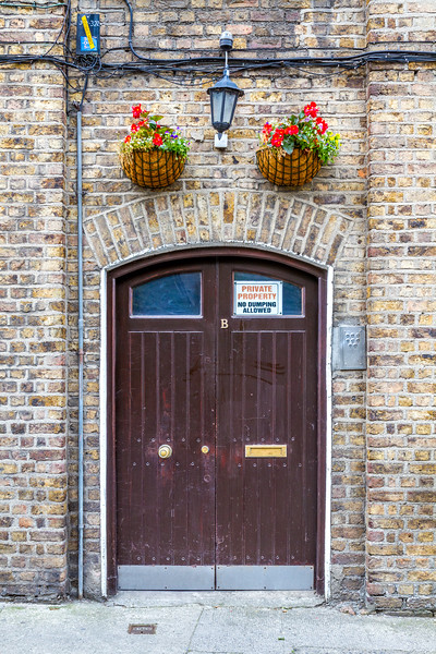 Brown double door with arch in brick wall and planters above with wall light - Dublin Ireland