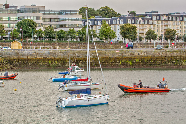 Rubber dinghy moving through sailboats in the bay at St Michaels Rowing Club in Dun Laoghaire County - Dublin Ireland