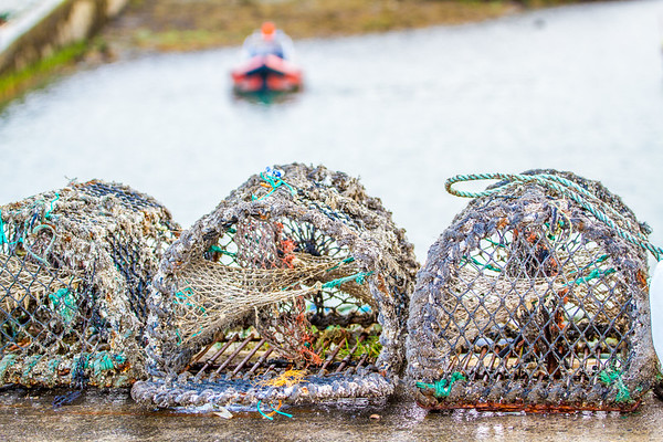 Crab traps in focus in forefront and rubber dinghy in the background OOF by St Michaels Rowing Club in Dun Laoghaire County - Dublin Ireland