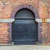 Old black arched door with in old brick wall with edge of arches on either side - Dublin Ireland