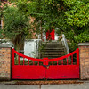 Red chained gate in brick wall with red door deeper in  - Dublin Ireland