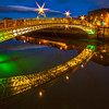 Ha'Penny bridge lit up during blue hour leading to Merchants Arch with light flares - Dublin Ireland