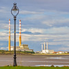 Lamp post on the shores of the Dublin Harbour at low tide with Poolbeg Generator Station in the background