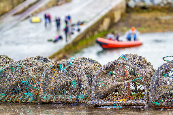 Crab traps in focus in forefront and Divers on a boat ramp in wetsuits in the background OOF by St Michaels Rowing Club in Dun Laoghaire County - Dublin Ireland