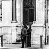 2 people standing outside the doors and pillars of The Royal Bank of Ireland College Green Branch - Dublin Ireland - BW