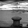 Sail boats in Dun Laoghaire Harbour inside of the East Pier, County Dun Laoghaire with bollard in forefront - Rathdown, Ireland - BW