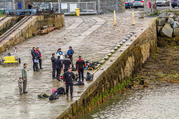 Divers on a boat ramp in wetsuits by St Michaels Rowing Club in Dun Laoghaire County - Dublin Ireland