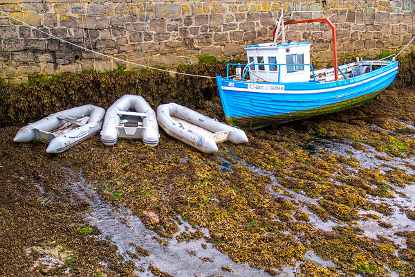 Small Irish fishing boat at low tide in Kinvarra Harbour - County Galway, Ireland