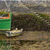 Stone stairs leading to Fairy Queen boat and small row boat in Kinvara Harbour at low tide - Ireland
