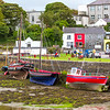 Boats in Kinvara Harbour at low tide with grass and buildings in the background - Ireland