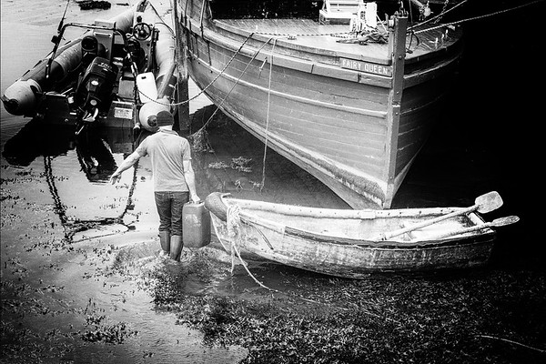 Fairy Queen boat in Kinvarra Harbour, rowboat and man taking plastic fuel tank to rubber dinghy - BW