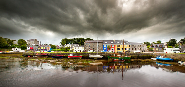 Kinvara Harbour - boats lined up on quay under dark stormy clouds  - panorama - Ireland