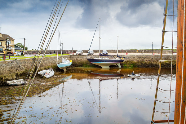 Kinvarra Harbour at low tide with boats docked - person rowing a rubber dinghy- County Galway, Ireland