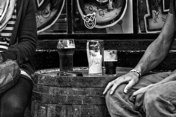Glasses of beer and ashtray on a barrel with a man and woman on each side - Dublin Ireland - BW - Wet Rocks