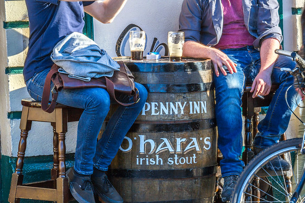 Ha'Penny Inn's O'Hara's Irish Stout Barrel and people with beer glasses on barrel - Dublin Ireland