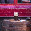 Guinness glass of beer, cigarettes, lighter and ashtray on a barrel in front of red window - Dublin Ireland