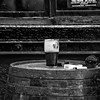 Guinness glass of beer, cigarettes, lighter and ashtray on a barrel in front of red window - Dublin Ireland - BW Wet Rocks