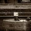 Guinness glass of beer, cigarettes, lighter and ashtray on a barrel in front of red window - Dublin Ireland - Sepia