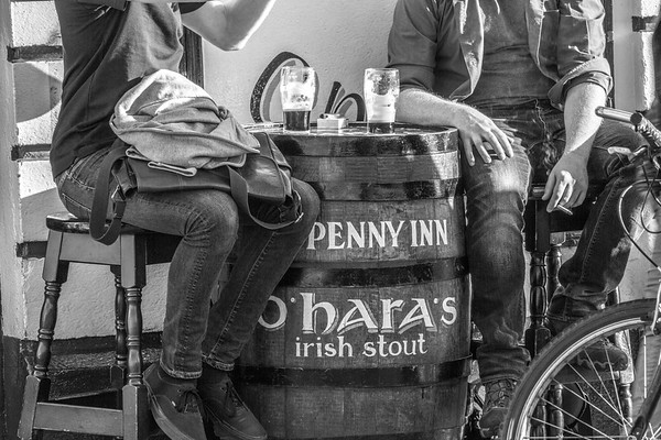 Ha'Penny Inn's O'Hara's Irish Stout Barrel and people with beer glasses on barrel - Dublin Ireland - BW