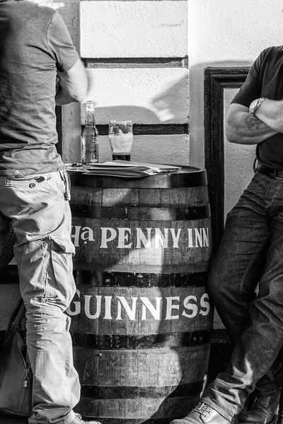 2 people standing aside a Ha'Penny Inn Guinness Barrel and beer on the top - Dublin Ireland