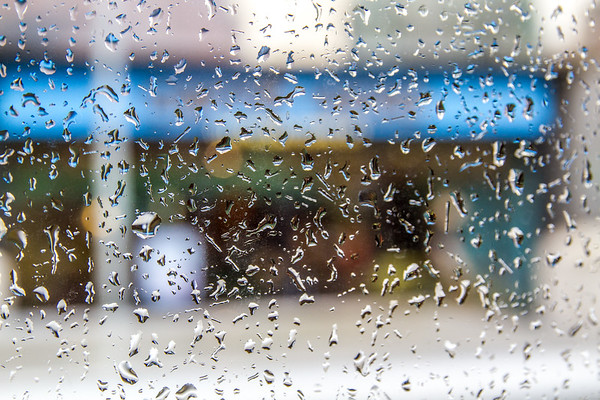 Rain drops on a window in front of colourful building OOF