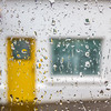Rain on a window in front of yellow door window and house OOF - Big Raindrops - landscape Ireland