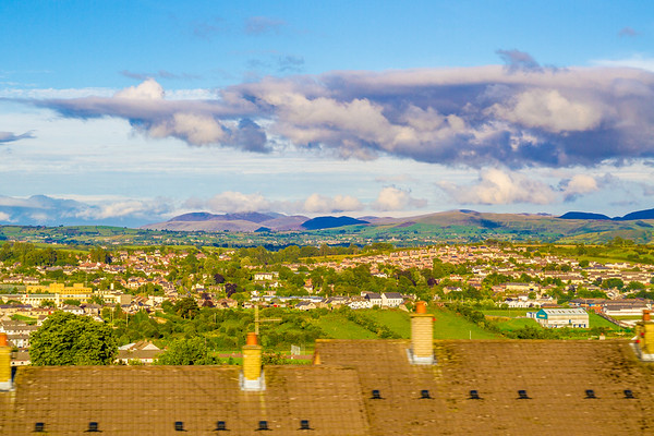Irish Hills and villages past roof line with chimneys - Northern Ireland