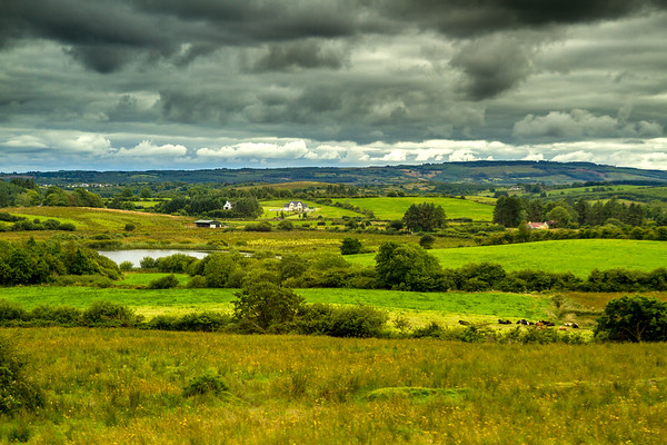 Irish fields and small lake under stormy clouds
