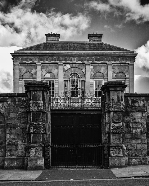 Old building behind stone wall - BW