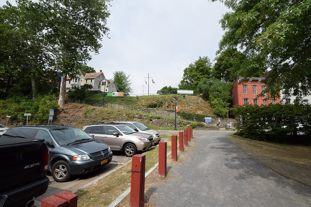 . From a municipal parking lot off West Strand Street, the proposed site of the Irish Cultural Center is above the stone wall that parallels Company Hill Path. The site is bounded by signs to the left and to the right, with flags at the center of the property.