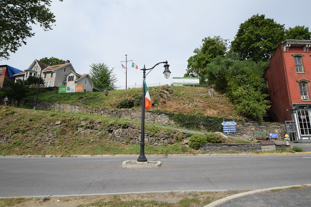 . From West Strand Street, the proposed site of the Irish Cultural Center is above the stone wall that parallels Company Hill Path. The site is bounded by signs to the left and to the right, with flags at the center of the property.